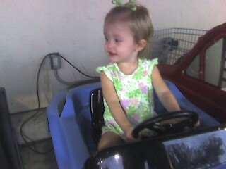 Ella rides the play car at HEB